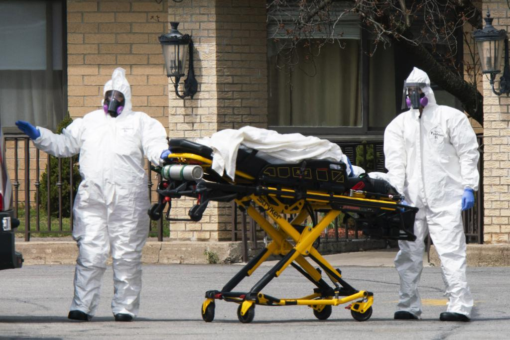 Workers wearing protective gear remove bodies of people who have died from COVID-19 from a New Jersey nursing home morgue. Photo: Eduardo Munoz Alvarez/Getty Images