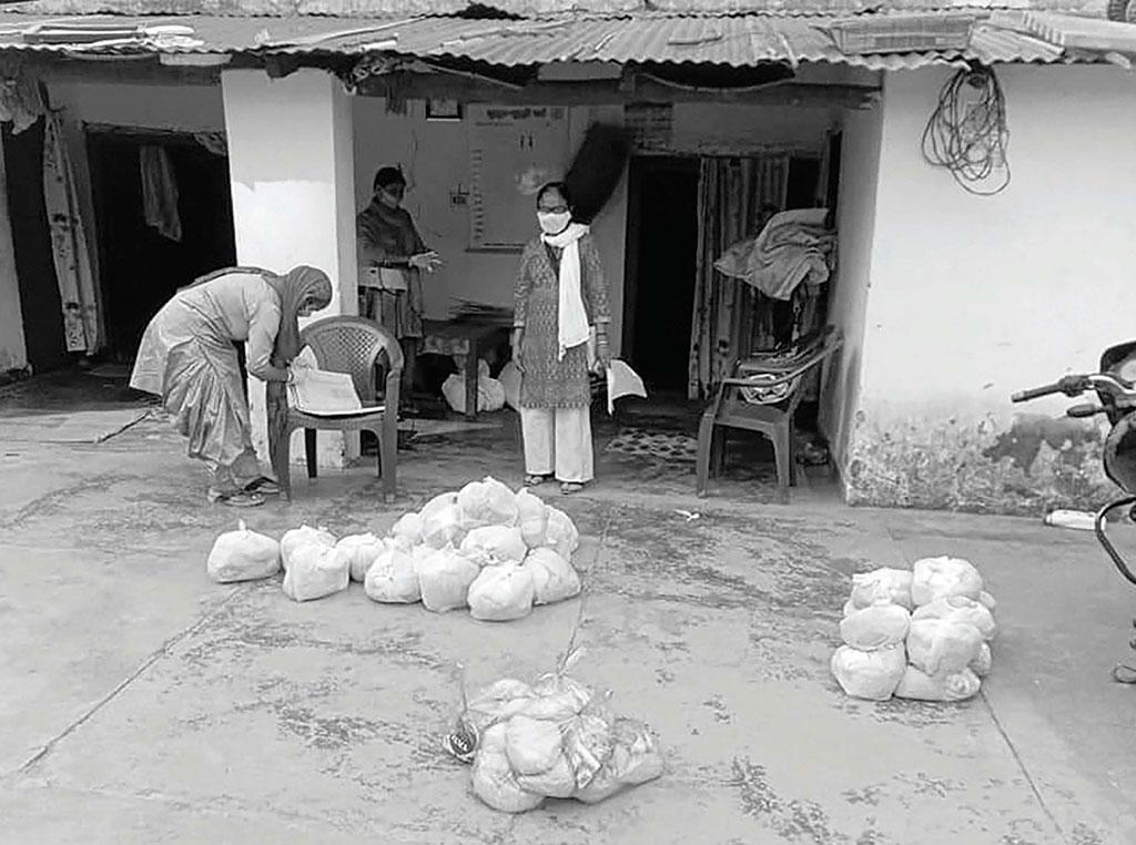 उत्तराखंड के देहरादून में आंगनवाड़ी कार्यकर्ता तीन महीने के लिए सूखे राशन के पैकेट तैयार कर रही हैं ताकि जरूतरमंदों तक इन्हें पहुंचाया जा सके  (फोटो: हर्षवर्धन बहुगुणा)