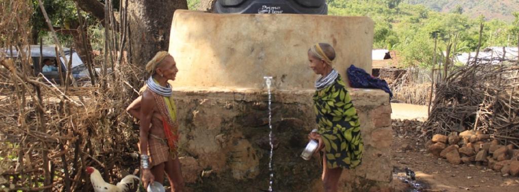 Two tribal women collect water outside water tank in Odisha's Rayagada district. Photo: Ashis Senapati