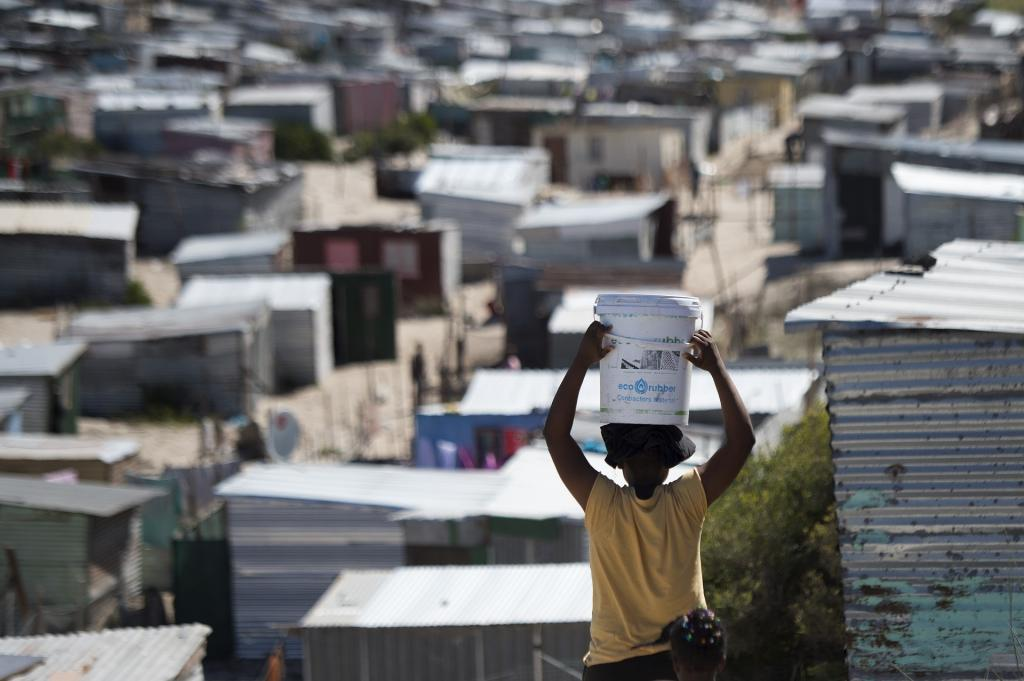 A woman carries a bucket of fresh water to an informal settlement in Khayelitsha,Cape Town. Photo: The Conversation