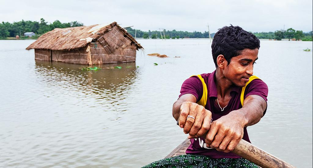 A boy rows past his submerged farms. The crisis has called out the need for essentials such as safe water, sanitation and physical distancing measures. Photo: Akash Basumatari