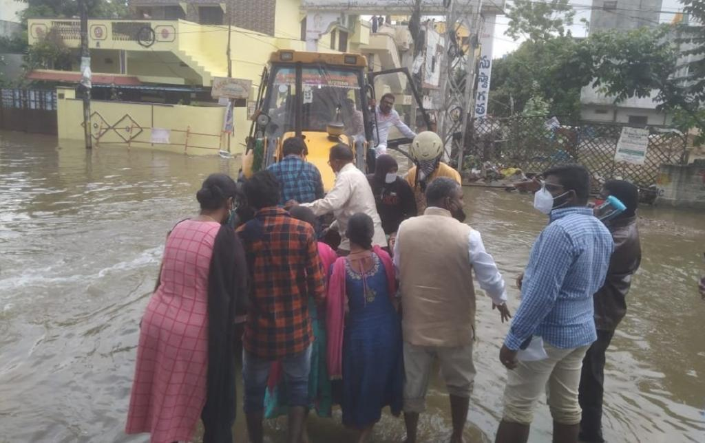 An earth mover rescues a family stranded due to floods in Malkajgiri: Telangana has received extremely heavy rainfall since October 13. Photo: Rachakonda Police @RachakondaCop / Twitter