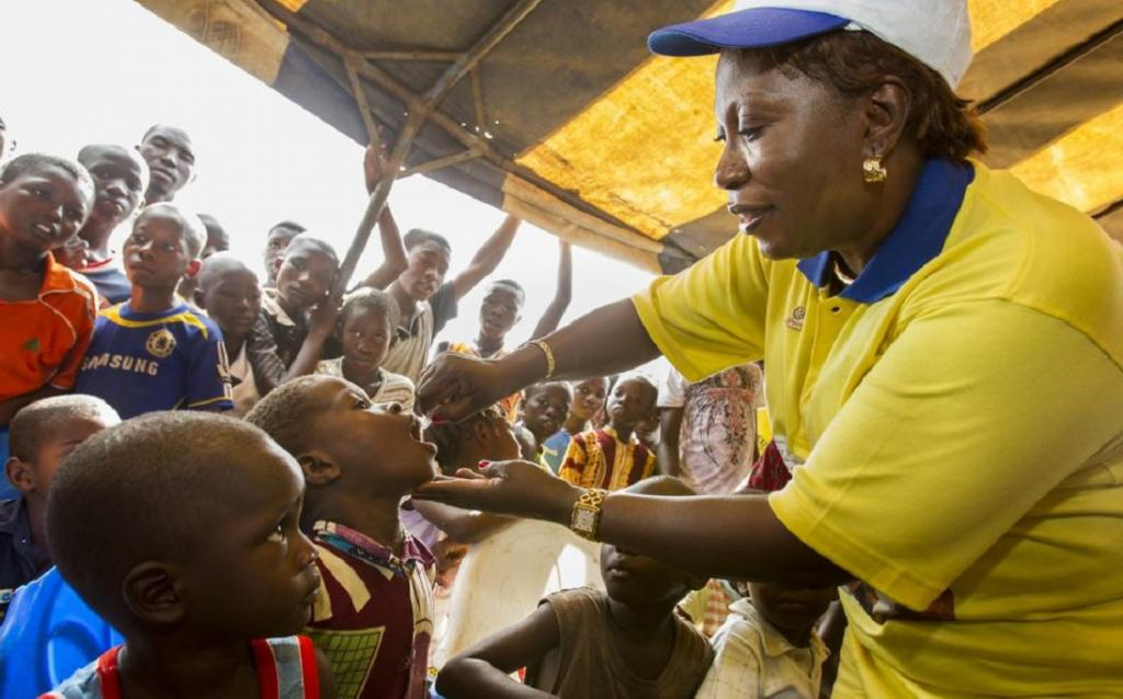 A female health worker vaccinates a child in Nigeria. Photo: Rotary International