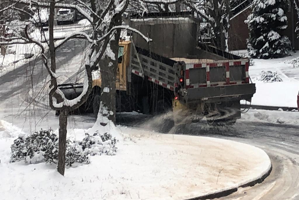 रोड पर जमा बर्फ को पिघलाने के लिए छिड़का जा रहा नमक; फोटो: सुजय कौशल