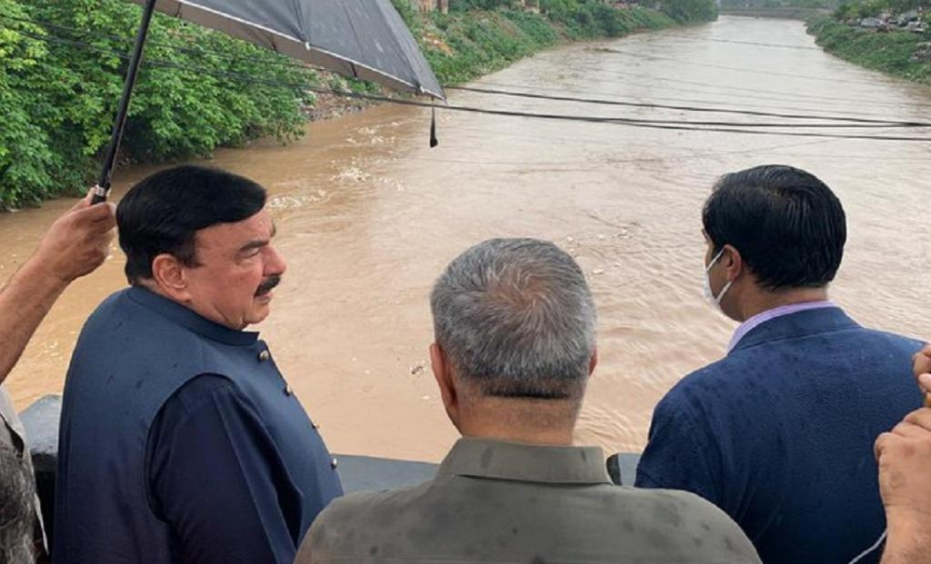 Pakistan's Interior Minister, Sheikh Rashid Ahmed looks at floodwaters from the Gawalmandi bridge to assess the flood situation in Rawalpindi. Photo: @ShkhRasheed / Twitter