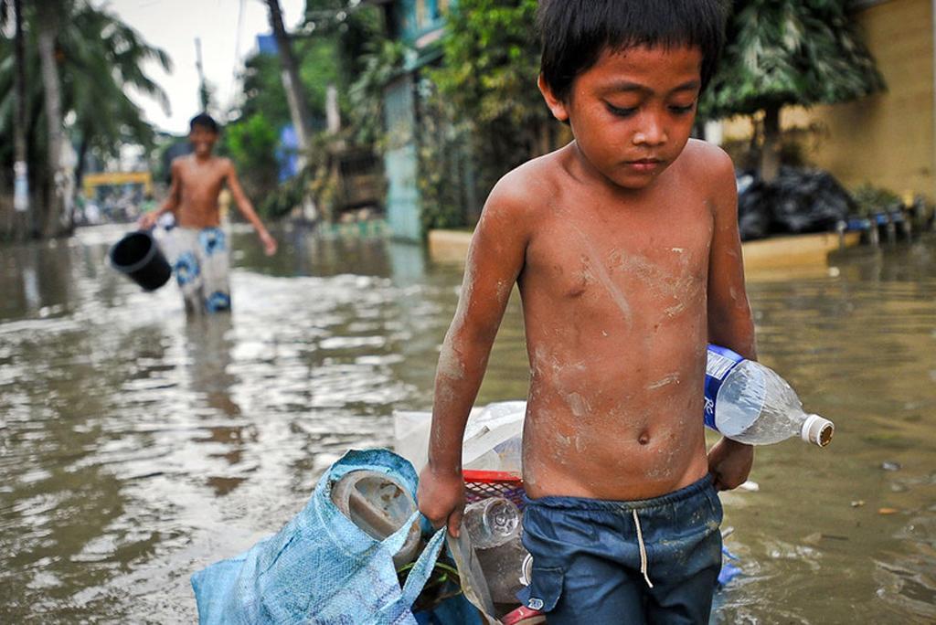 मनीला में तूफान के बाद आई बाढ़ में अपने सामान को घसीटता एक बच्चा, फोटो: एशियन डेवलपमेंट बैंक (एडीबी)