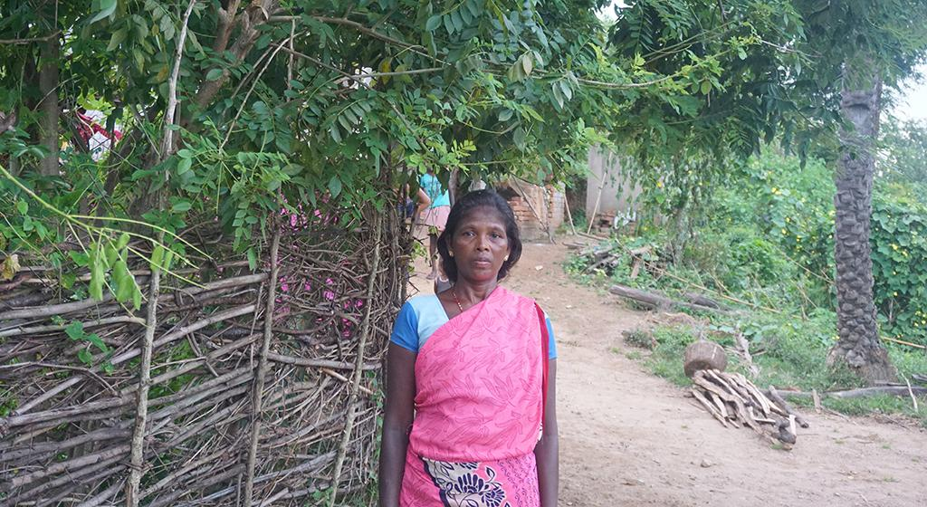 Sumi Soren (43) belongs to the Santhali tribe standing near the Gliricidia plant. The plant is used to feed goats and is highly nutritious for the growth of goats.