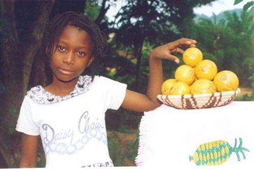 A girl displays a basket of Srychnos coculoides (monkey orange) in Malawi