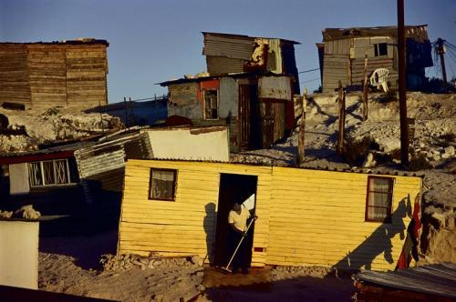 A woman sweeps outside her shack in Khayelitsha, Cape Town. South Africa is among the most unequal societies in the world. Photo: Getty Images / Conversation