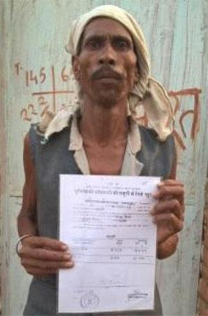 Ram Manohar Kaundar, a tribal from Singaro village of Madhya Pradesh, shows his land rights document  (Credit: Kundan Pandey)