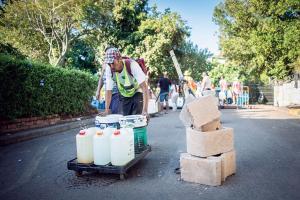 केपटाउन में सपाट ट्रोली को ऊबर सेवा के नाम से बुलाया जा रहा है। इसके जरिए  पानी के गैलनों को कारों तक पहुंचाते हुए देखा जा सकता है (मॉर्गन ट्रिम्बल)