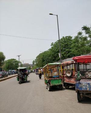 The e-rickshaw drivers park their vehicle in a long line at the corner of the road