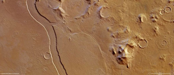 Topographic view of Reull Vallis: The sides of Reull Vallis are particularly sharp and steep in these images, with parallel longitudinal features covering the floor of the channel itself. These structures are believed to be caused by the passage of loose debris and ice during the 'Amazonian' period (which continues to this day) due to glacial flow along the channel.The structures were formed long after it was originally carved by liquid water during the Hesperian period, which is believed to have ended between 3.5 billion and 1.8 billion years ago