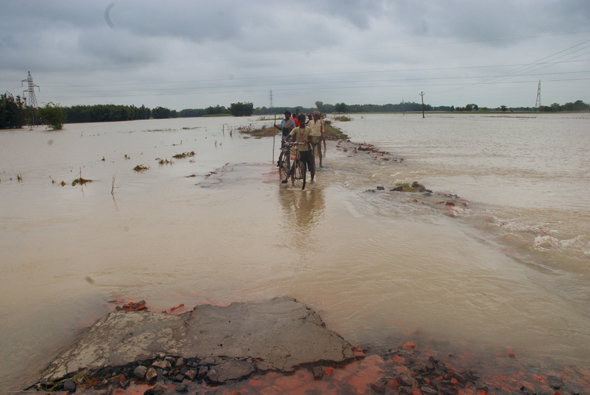 A family is stranded as rainwater sweeps away what used to be a road in this village.Read also:  Century of rainfallPhotograph by: Meeta Ahlawat