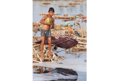 A child looks curiously at the waste accumulated on the Yamuna bank to find something interesting Photo By: Meeta Ahlawat