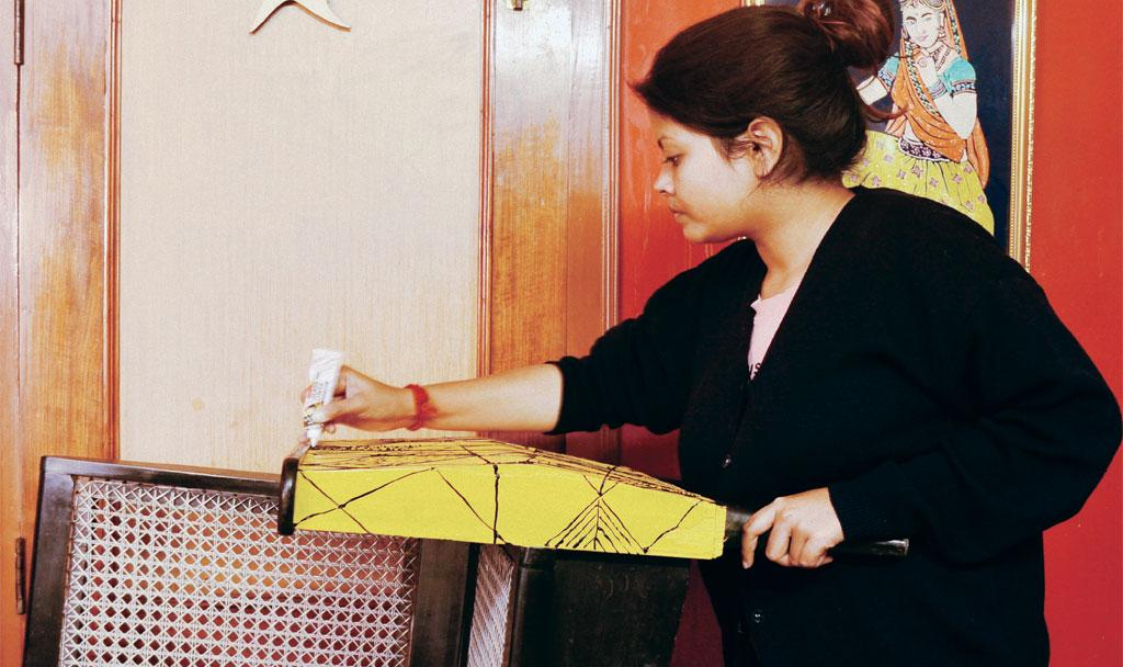 Neelakshi Devi, founder of Axomnia, paints an old sofa to give it a new look
