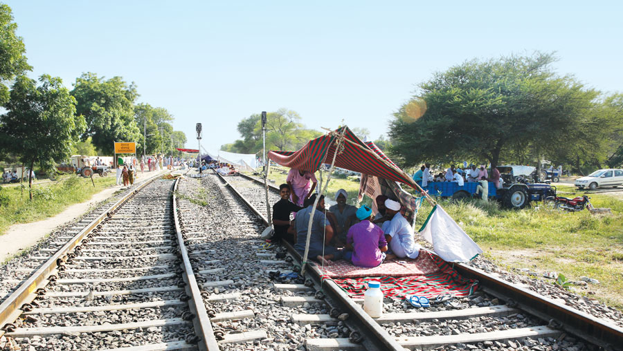 Farmers set up camps on tracks near Sher Garh railway station in Bathinda to demand government support after the whitefly attack destroyed their cotton crops