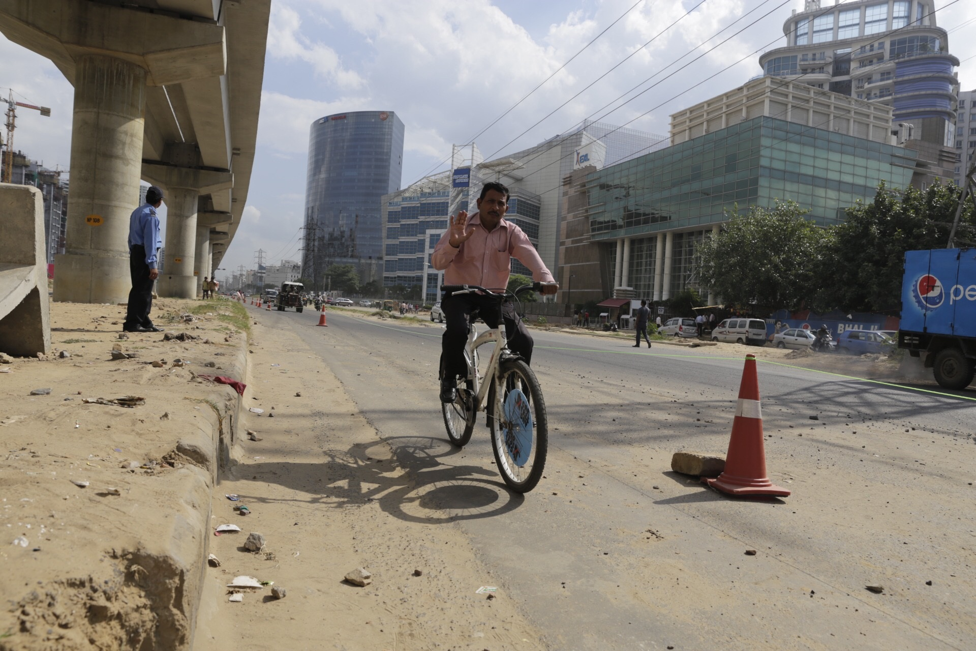 A man waves as he rides his bicycle in Gurgaon on Tuesday. Tracks were especially created to ensure smooth passage to cyclists