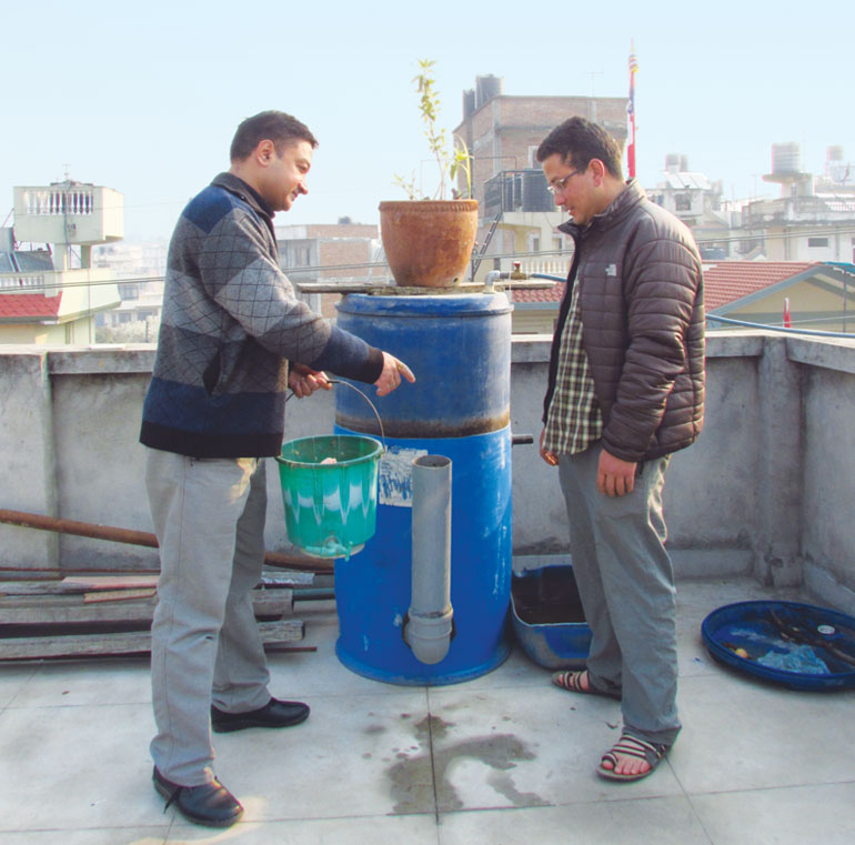 Prakash Amatya (left) of Guthi, a non-profit, explains to Ravi Dangol, a resident of Kathmandu, how to run the biogas unit (Photo: Prakash Amataya)
