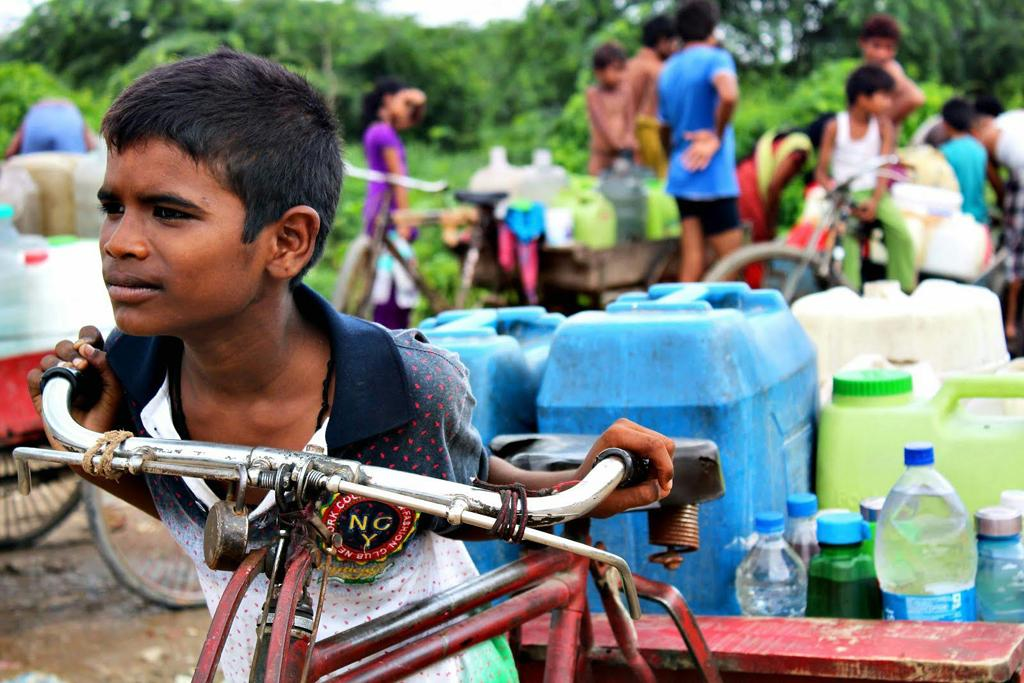 A boy pushes a cart laden with water. Old jerry cans, water bottles, paint containers, soft drink bottles, buckets—anything can be used as a vessel. Reusing such plastics is a matter of necessity