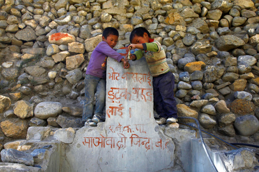 Two boys play at a dried water tap with Maoist graffiti in Yara.